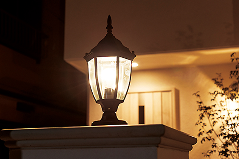 門柱の上にガーデンライト。アイアンのフレーム越しに、上品な灯りが温かい。