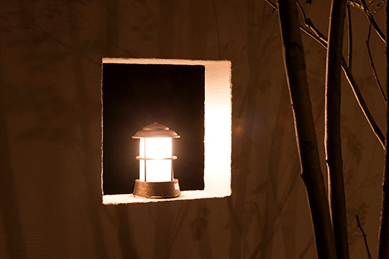 外壁に化粧された窓には、可愛らしいライト。優しい雰囲気が特徴。