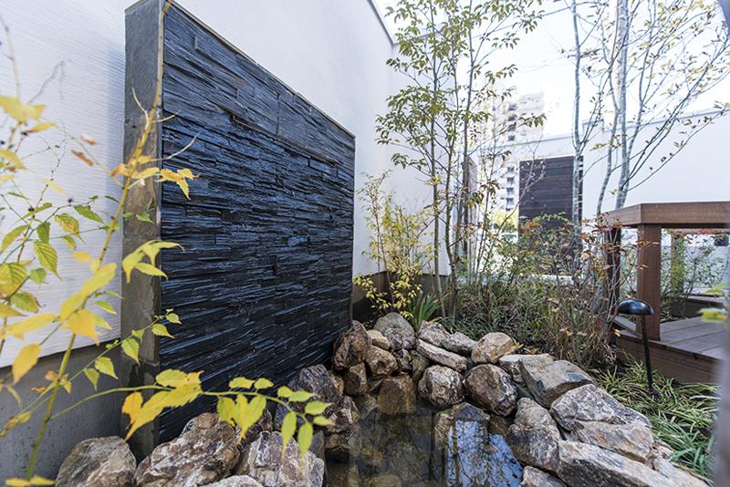 壁泉の周囲には植栽が施され、季節感が感じられる空間に。