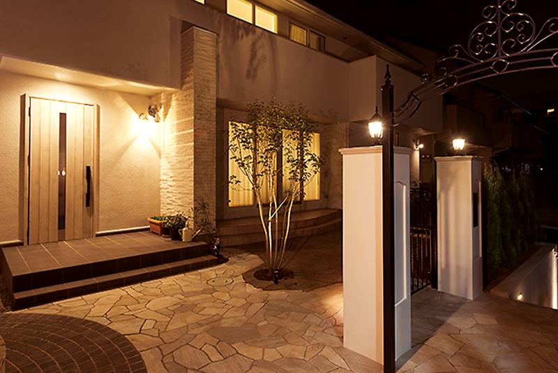 乱形石とタイルを組み合わせたアプローチ。ライトに照らされて、より上品な空間に。