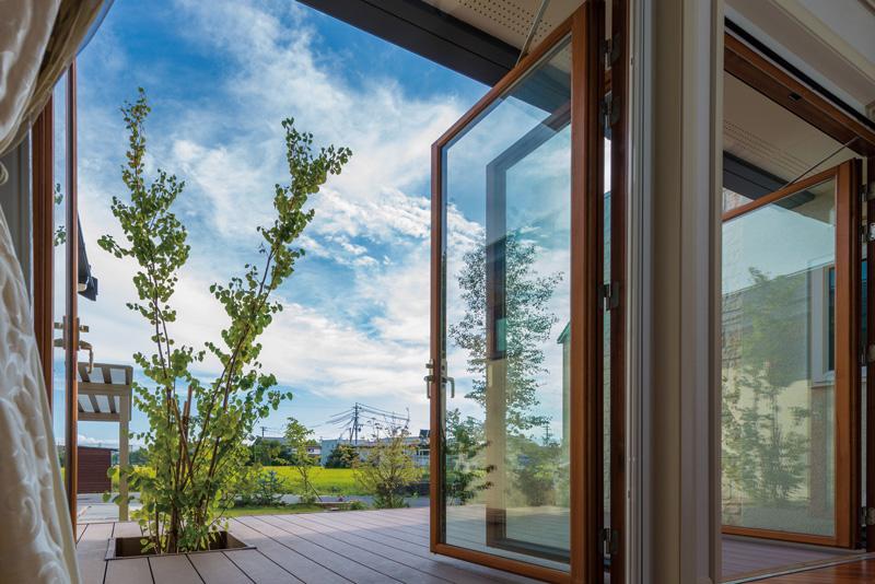 リビングルームの窓を開け放ち、デッキ越しに眺めるお庭。