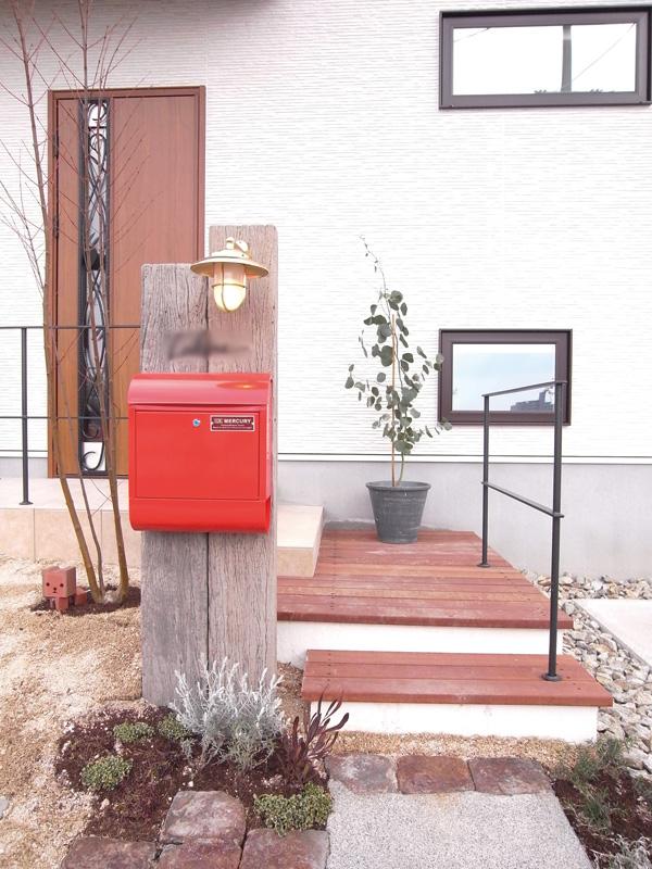 古木を利用した門柱に、住む人のこだわりで組み合わせた真っ赤なポスト