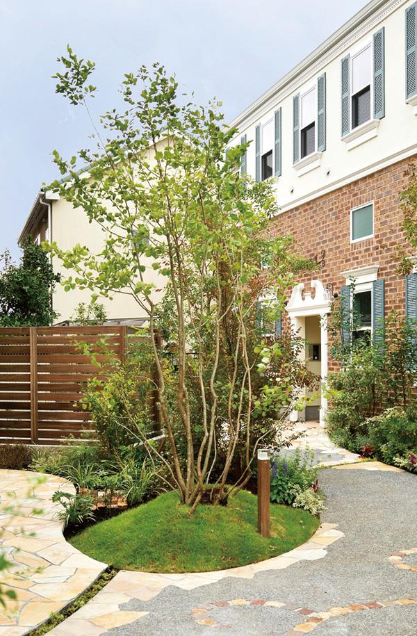 乱形石と自然素材を組み合わせたアプローチとシンボルツリーが、住まいに人を迎え入れる。