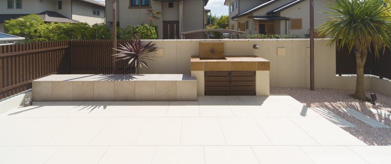 タイルデッキのお庭。外壁と一体化したデザインのガーデンシンクとベンチの造作で高級感のある仕上がりに。