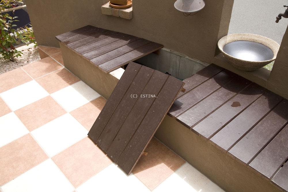 壁に沿ってスペースを有効に使ったウッドベンチ。 腰かけるだけでなく、ガーデニンググッズの収納庫としても使えるよう工夫している。