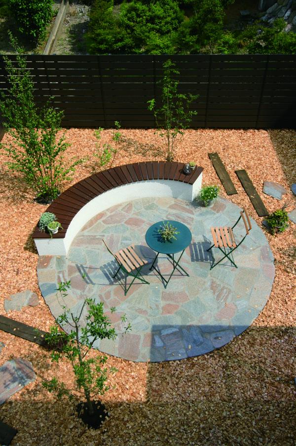 円形の石貼りテラスは落ち着いた色味にし、ベンチ座面の木材や樹木となじませた。 ウッドチップを敷き、森林の香りを楽しめるお庭。