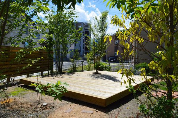樹木やウッドフェンスで外からの視線を遮り、広い敷地を贅沢に使ったウッドデッキ。